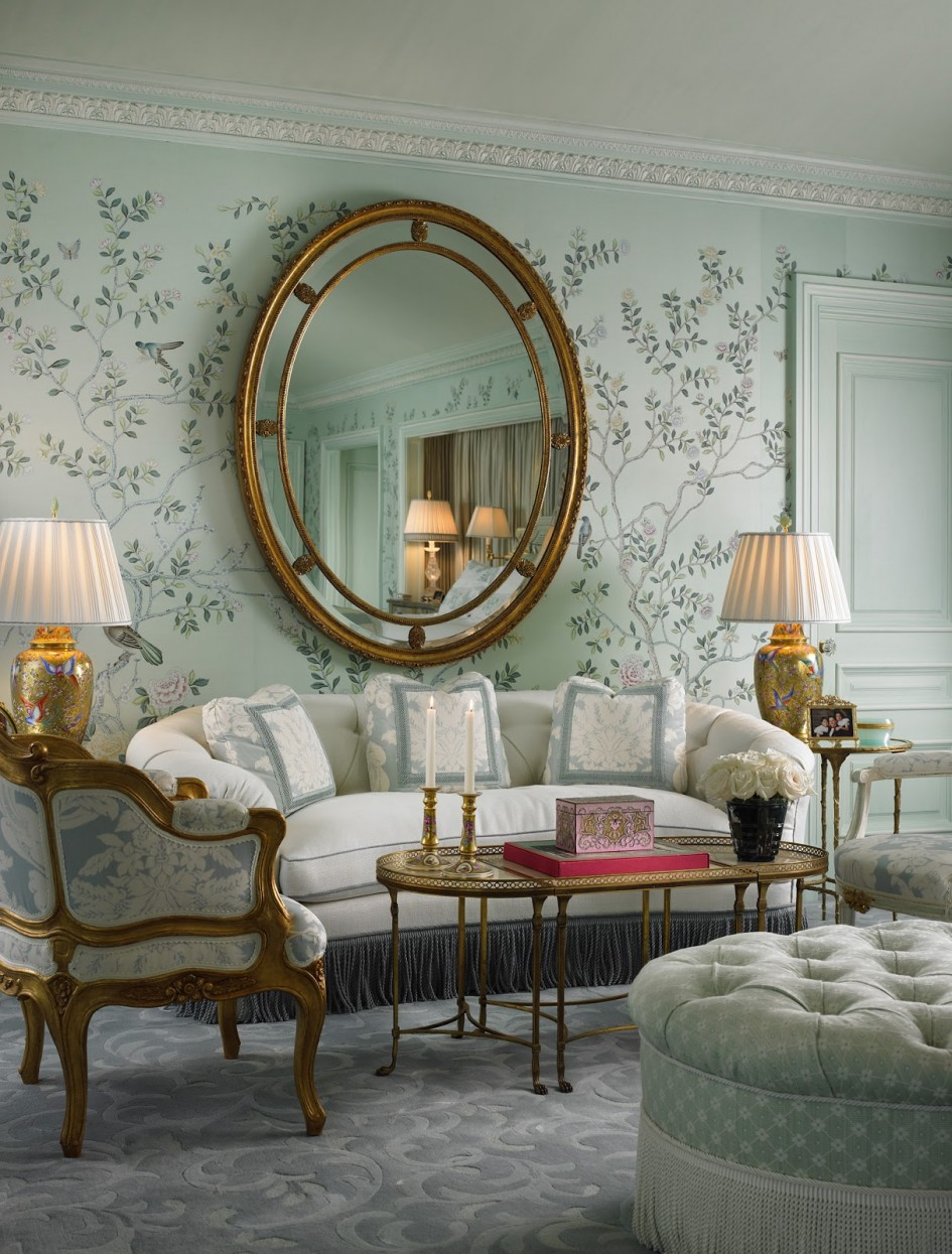living-room-mirror-wall_round-gold-frame-finish-metal-wall-mirror_white-leaves-interior-wall-decoration_bluish-polka-dot-storage-ottoman-with-tassels_grey-white-damask-floor-carpet_victorian-furniture
